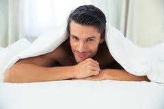 Man som ligger under filten i sängen royaltyfri fotografi