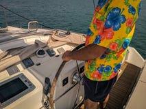 Man som lotsar fartyget med den kulöra t-skjortan royaltyfria bilder