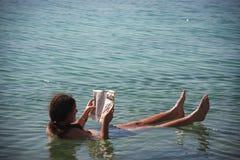 Man som läser en tidning i det döda havet Arkivfoton