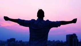 Man som lyfter händer på soluppgångbakgrund, frihet och inspiration, baksidasikt arkivfilmer