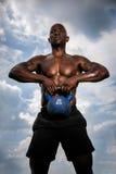 Man som lyfter tung kettlebell Fotografering för Bildbyråer