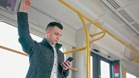 Man som lyssnar till musik från smartphonen med hörlurar, när resa med drevet lager videofilmer