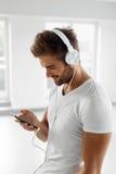 Man som lyssnar till musik i hörlurar genom att använda mobiltelefonen inomhus Royaltyfri Bild