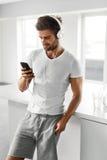 Man som lyssnar till musik i hörlurar genom att använda mobiltelefonen inomhus Fotografering för Bildbyråer