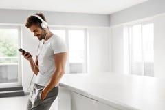 Man som lyssnar till musik i hörlurar genom att använda mobiltelefonen inomhus Royaltyfria Foton