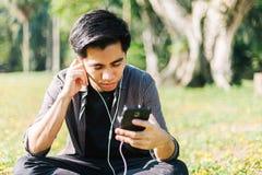 Man som lyssnar till musik på hans apparat Arkivfoton