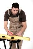Man som mäter trä Arkivfoto