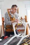 Man som målar en stol i hans seminarium Arkivbild
