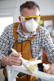 Man som målar en stol i hans seminarium Royaltyfri Foto