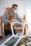 Man som målar en stol i hans seminarium Royaltyfri Fotografi