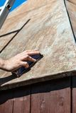 Man som maler taket av en friggebod med ett sandpappra kvarter, rus Royaltyfri Fotografi
