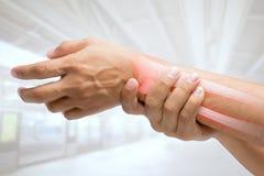 Man som masserar den smärtsamma handleden fotografering för bildbyråer