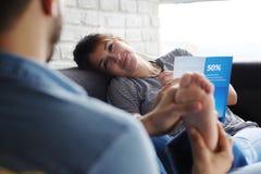 Man som masserar flickvänfot på Sofa At Home Arkivbild
