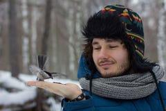 Man som matar en fågel från handen Arkivfoton