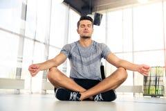 Man som mediterar i konditionidrottshall Royaltyfri Foto