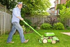 Man som mejar gräsmatta Fotografering för Bildbyråer