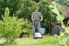 Man som mejar gräsmatta i trädgård Arkivbild