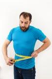 Man som mesuaring hans mage Royaltyfri Foto
