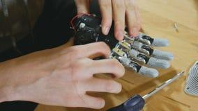Man som monterar den innovativa cybernetic bioniska armen Högteknologisk innovativ prosthetics arkivfilmer