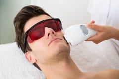 Man som mottar behandling för laser-hårborttagning Arkivfoto