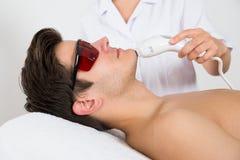 Man som mottar behandling för laser-hårborttagning Royaltyfri Fotografi