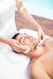 Man som mottar en ansikts- massage från massör royaltyfria bilder