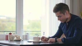 Man som ner skriver information från smartwatchen glidare 4K arkivfilmer