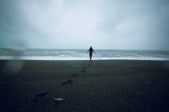 Man som oing på den svarta sandstranden på Island Arkivbild