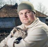 Man som omfamnar en goatling. Royaltyfri Foto