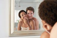 Man som omfamnar kvinnan som applicerar läppstift i spegel Arkivbild