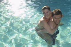 Man som på ryggen ger kvinnan i simbassäng royaltyfri bild