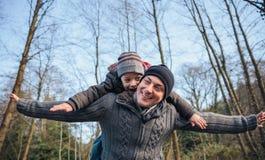 Man som på ryggen ger ritt till den lyckliga ungen i skogen royaltyfri bild