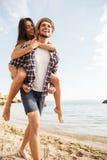 Man som på ryggen ger ritt till hans flickvän på stranden Fotografering för Bildbyråer