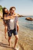 Man som på ryggen ger ritt till hans flickvän på stranden Arkivfoton