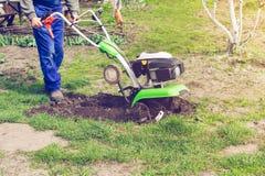 Man som på våren arbetar trädgårds- med rorkultmaskinen royaltyfria bilder