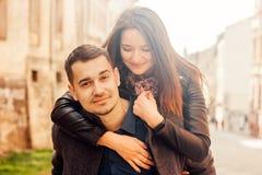 Man som p? ryggen ger ritt till hans flickv?n Lyckliga par i gata royaltyfri foto