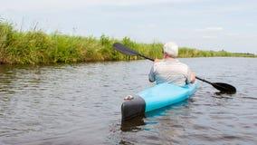 Man som paddlar i en blå kajak royaltyfri fotografi