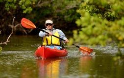 Man som paddlar i en kajak i Florida Arkivfoto