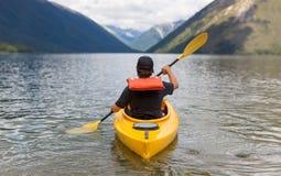 Man som paddlar kajaken i bergsjön Arkivfoton