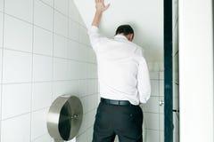 Man som peeing i toalett Arkivfoto