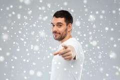 Man som pekar fingret till dig över snöbakgrund Arkivfoton