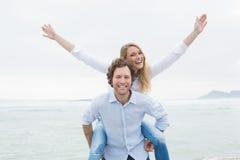 Man som piggybacking kvinnan på stranden Royaltyfria Bilder