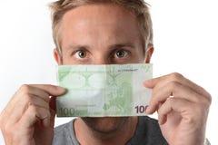 Man som plirar över en eurosedel Royaltyfri Foto