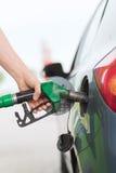 Man som pumpar bensinbränsle i bil på bensinstationen Arkivfoto