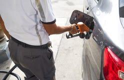 Man som pumpar bensinbränsle i bil på bensinstationen Arkivbilder