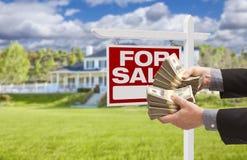 Man som räcker över pengar i Front House For Sale, tecken royaltyfri bild