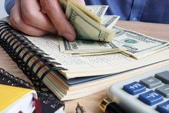 Man som räknar dollarräkningar Skrivbord med räknemaskinen, huvudboken och dollar royaltyfria bilder