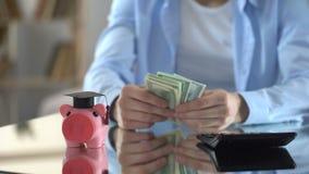 Man som räknar kostnader för utbildning, pengar för universitetet, investering i framtid arkivfilmer