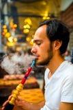 Man som röker den turkiska vattenpipan Arkivbild
