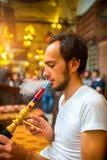 Man som röker den turkiska vattenpipan Fotografering för Bildbyråer